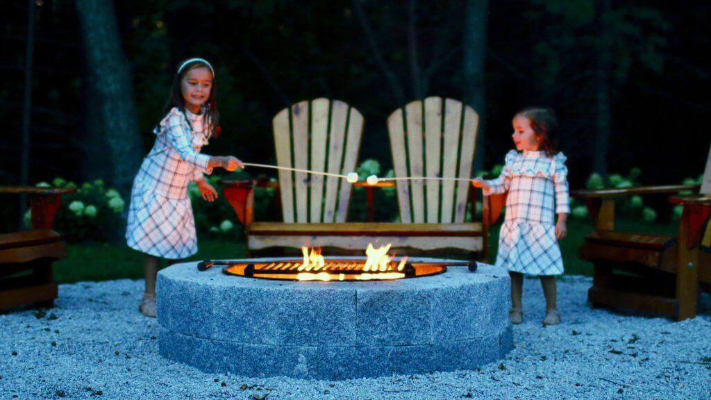 Photo of children roasting marshmallows at a fire pit